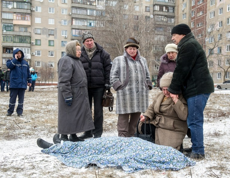 Relatives stand beside the body of a victim of a shelling in Kramotorsk on February 10, 2015