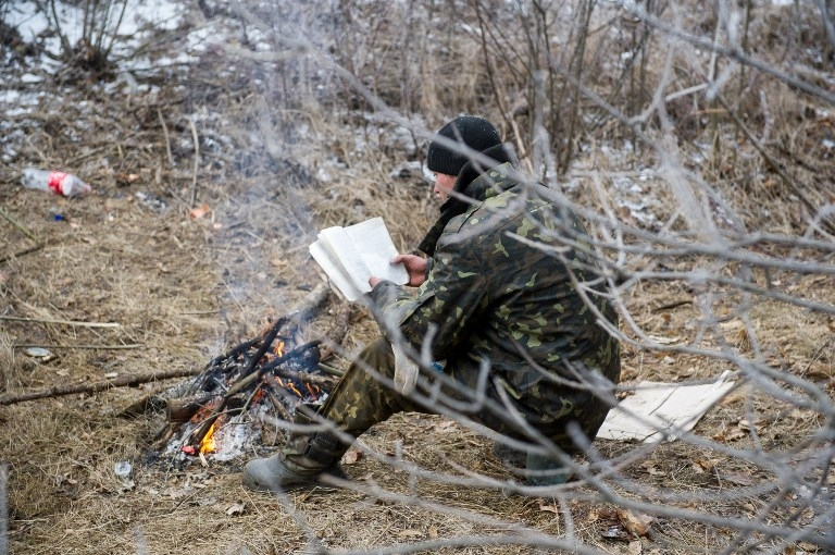 An Ukrainian soldier reads a book during a ceasefire in Svitlodarsk on February 15, 2015