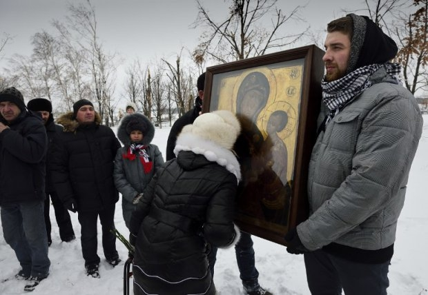 A woman kisses an icon of Our Lady of Tikhvin at the Savur-Mogyla memorial