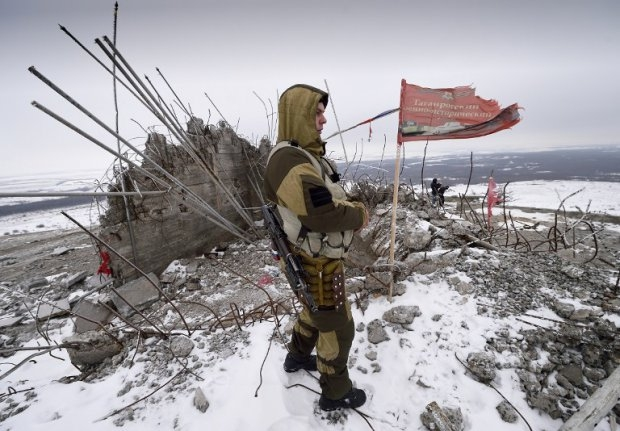 A Donetsk People's Republic fighter looks out over the damaged Savur-Mogyla memorial