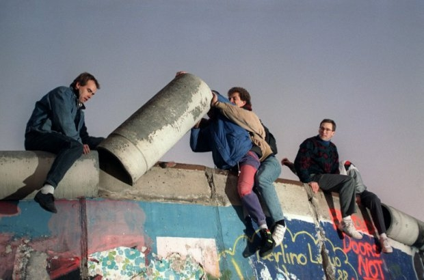 Young West Berliners, perched on top of the Berlin Wall, remove a piece of it, on November 16, 1989 (AFP Photo / Patrick Hertzog)