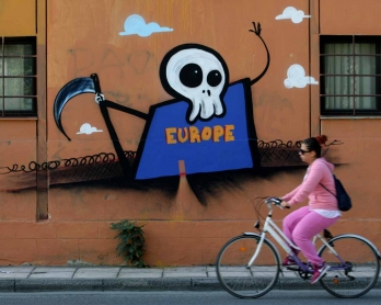 A woman rides her bike past a graffiti depicting Europe as the Grim Reaper, with a small door opening through its wall-like body and a barbed wire fence, in Thessaloniki on 4 October, 2015.