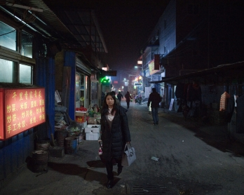 This picture taken on February 15, 2017 shows a woman walking on a street in the Heiqiaocun migrant village in Beijing.