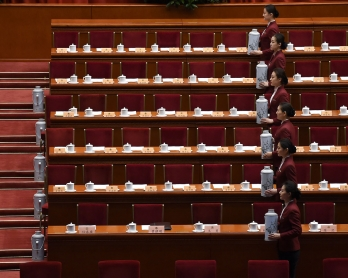 Chinese hostesses prepare for the closing session of the Chinese People's Political Consultative Conference (CPPCC) at the Great Hall of the People in Beijing on March 13, 2017.