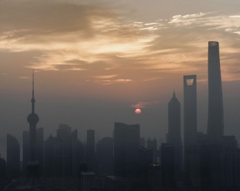 In this picture taken on September 9, 2016, the sun rises over the financial district of Pudong in Shanghai.