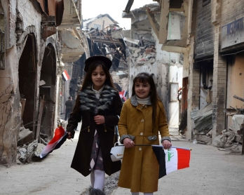 Iraqi girls walk holding their national flag towards a ceremony for the re-opening of the Bab al-Saray market in the old city of Mosul on January 11, 2018. -  (Photo by Ahmad MUWAFAQ / AFP)