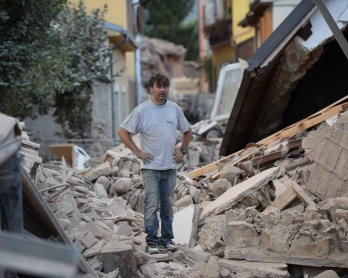 A man stands on a damaged home after a strong earthquake hit Amatrice on August 24, 2016.