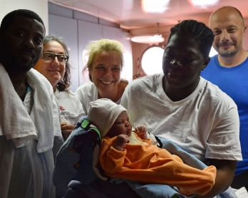 Bernadette Obiona and David Dibonde (L) pose with their newborn Alex with Angelina Perri from Italy (2ndL), a nurse working for French NGO Medecins Sans Frontieres, doctor Erna Rijnierse (C) from Netherlands and the captain of the
