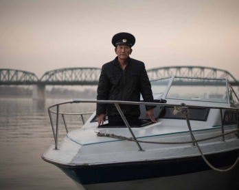 Sailor Kim Il-Soo poses for a phot on a boat used to host wedding photo shoots on the Taedong river in Pyongyang.