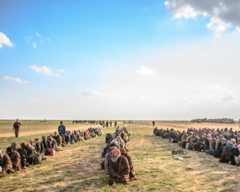 Men suspected of being Islamic State (IS) fighters wait to be searched by members of the Kurdish-led Syrian Democratic Forces (SDF) after leaving the IS group's last holdout of Baghouz, in Syria's northern Deir Ezzor province on February 22, 2019.