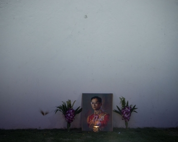 A lit candle and flowers adorn an image of the late Thai King Bhumibol Adulyadej on the outer wall of the Grand Palace at dawn on October 16, 2016.