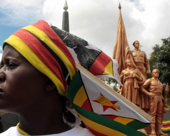 A supporter of Zimbabwean President Robert Mugabe's ruling ZANU-PF attends the funeral of Harare Governor David Karimanzira at the National Heroes Acre in Harare on March 27, 2011.