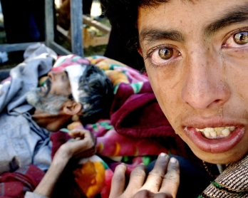 Tears roll down from the eyes of earthquake victim Mumtaz (R) as he waits with his badly injured father Noordin for evacuation to Chakoti in the Pakistan controlled Kashmir, 13 October 2005, five days after a powerful earthquake shattered the region