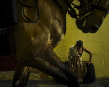 A horseman rides past a dancer warming up backstage during the Bullfighting Day at the Campo Pequeno bullfighting arena in Lisbon on February 23, 2019. - The 'Corrida' explained to children, followed by a bloodless show: bullfighters in Portugal are tryin