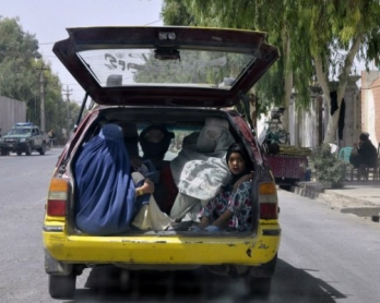 Afghan women ride in the back of a taxi in a street in Kandahar on September 16, 2013.