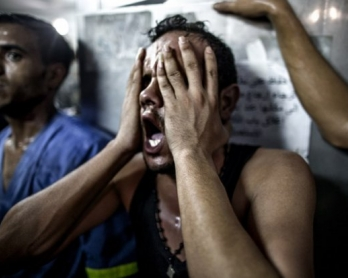 A relative reacts after seeing the bodies of three Palestinian children, killed in an explosion in a public playground on the beachfront of Shati refugee camp. July 28, 2014.