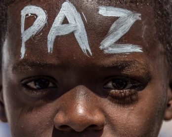 A boy with the word 'Peace' written on his forehead at a march in Rio's Complexo do Alemao favela on April 4, 2015 held after a 10-year-old boy was shot dead by police during a showdown with drug traffickers