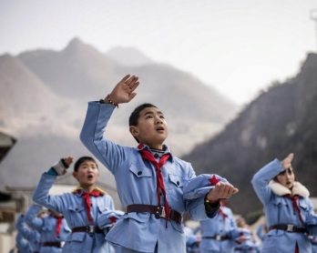 Pupils sing after raising the national flag at the Beichuan Red Army primary school on January 21, 2015