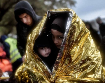 Children huddle under emergency blankets after arriving in Lesbos in October.