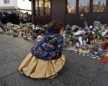 A child outside a memorial to victims at the Petit Cambodge restaurant.