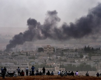 Kurdish people look at smoke rising from Kobane on October 11, 2014 (AFP Photo / Aris Messinis)