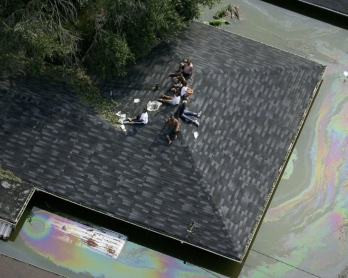 People are stranded on a roof due to flood waters from Hurricane Katrina on August 30, 2005 in New Orleans