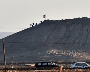 Alleged Islamic State group militants stand next to an IS flag atop a hill in the Syrian town of Kobane, as seen from the Turkish-Syrian border on October 6, 2014