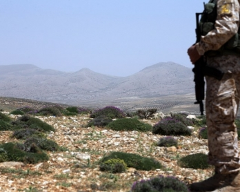 A Hezbollah fighter stands on a hill on the Lebanese side of the Qalamun mountains on the border with Syria on May 20, 2015