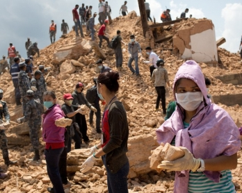 Nepalese civilians and police clear rubble at a temple in Kathmandu on May 2, 2015, a week after a 7.8 magnitude earthquake struck the Himalayan nation