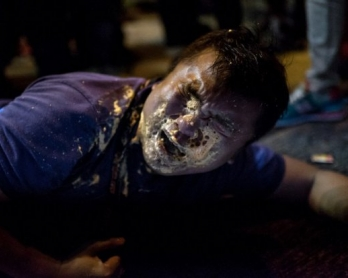 """A Hong Kong journalist collapses in agony after being hit in the face with pepper spray by police in the Mongkok district of Hong Kong on October 17, 2014"