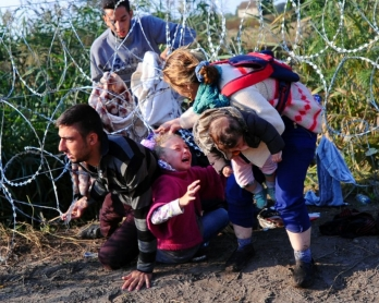 A family crawls under the Hungarian-Serbian border fence near Roszke on August 27, 2015 (AFP Photo / Attila Kisbenedek)