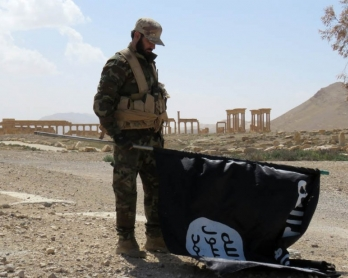 A member of the Syrian pro-government forces carries an Islamic State (IS) group flag in the ancient city of Palmyra on March 27, 2016 (AFP)