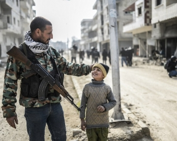 A Kurdish fighter and his son in the center of Kobane, Syria on January 28, 2015