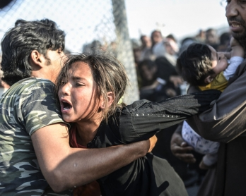 Syrians fleeing the war rush through broken down border fences to enter Turkish territory, near the border crossing at Akcakale in Sanliurfa province on June 14, 2015