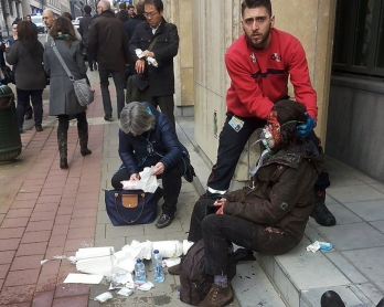 A private security guard helps a wounded woman outside the Maalbeek metro station in Brussels on March 22, 2016