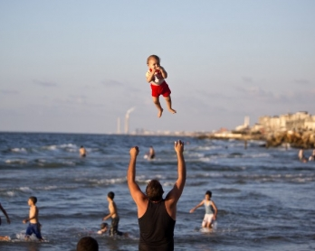 A man and his baby on a beach in Gaza City on September 7, 2014